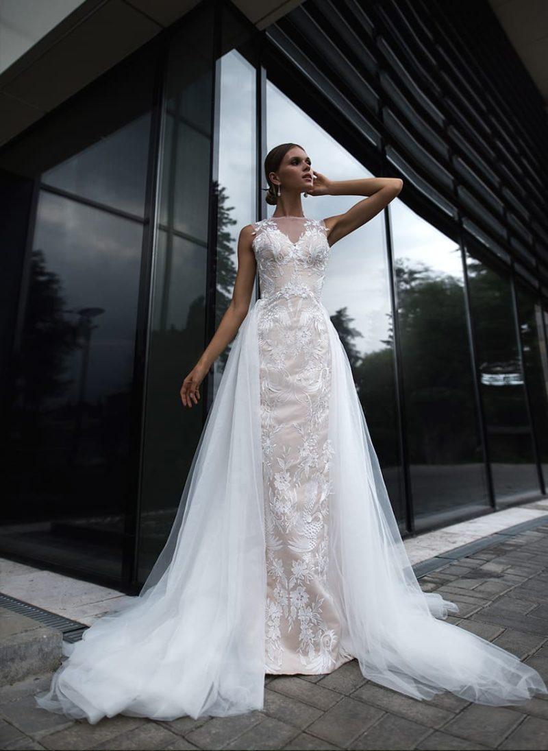 Бежевое свадебное платье с кружевной отделкой и белым пышным шлейфом.