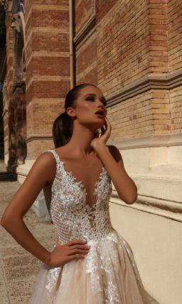 Бежевое свадебное платье с белой кружевной отделкой и многослойным низом.