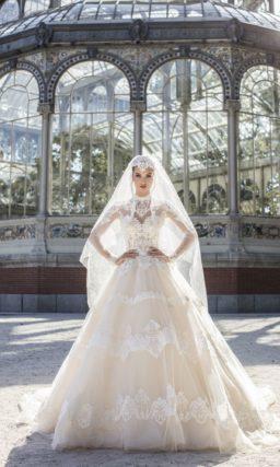 Бежевое свадебное платье с длинным прозрачным рукавом и пышной юбкой.