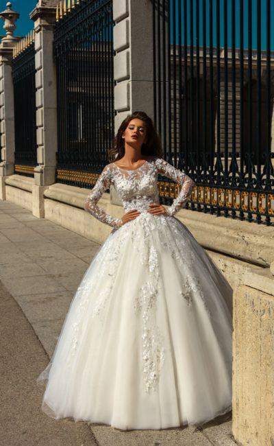 Пышное свадебное платье с длинным полупрозрачным рукавом и кружевным декором.