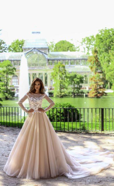 Бежевое свадебное платье пышного кроя с длинным рукавом и стильным шлейфом.