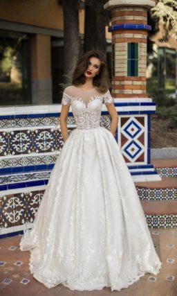 Пышное свадебное платье с кружевным декором и закрытым верхом.