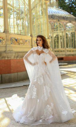 Открытое свадебное платье с длинной накидкой и пышной юбкой.