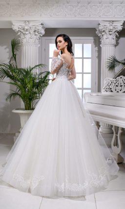 Пышное свадебное платье с прозрачным рукавом и открытой спинкой.