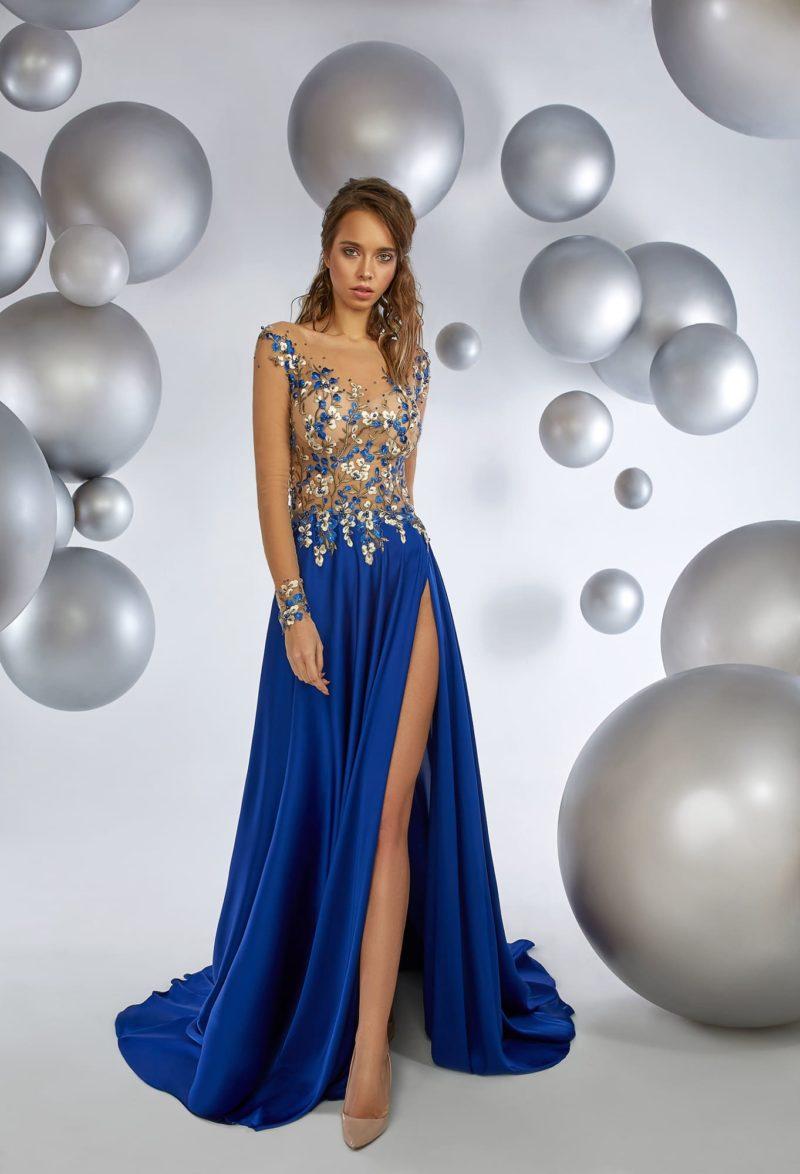 Прямое вечернее платье с полупрозрачным верхом и длинной синей юбкой.