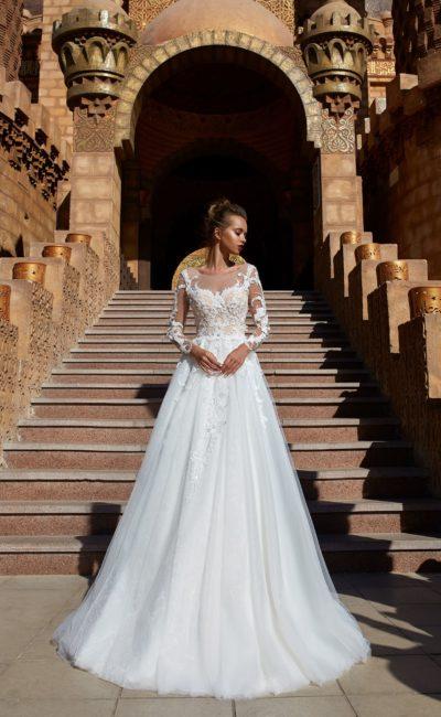 Свадебное платье пышного силуэта с длинным полупрозрачным рукавом.