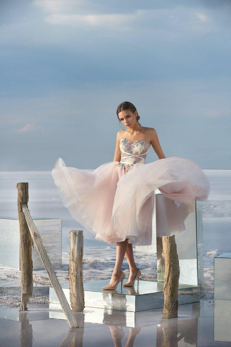 Розовое вечернее платье длиной чуть ниже колена с открытым декольте.