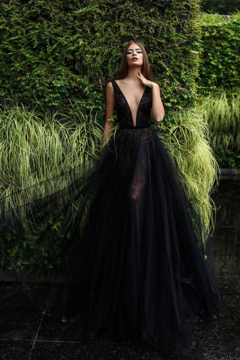 Черное вечернее платье с пышной многослойной юбкой и открытым верхом.