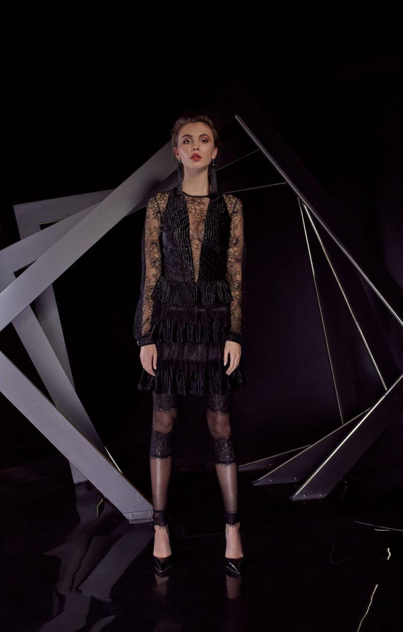 Черное вечернее платье с юбкой длины миди, дополненное кружевным рукавом.