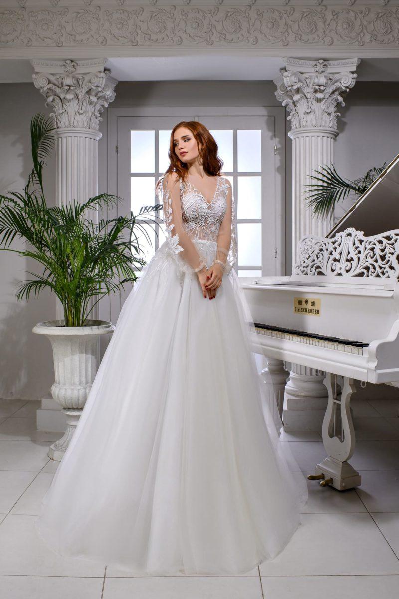Нежное свадебное платье с длинным прозрачным рукавом и открытой спинкой.