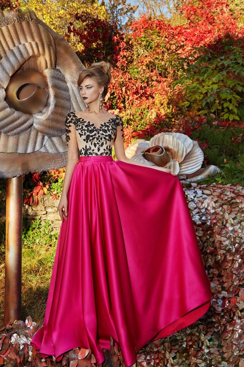 Вечернее платье с черной отделкой лифа и малиновой юбкой из атласа.