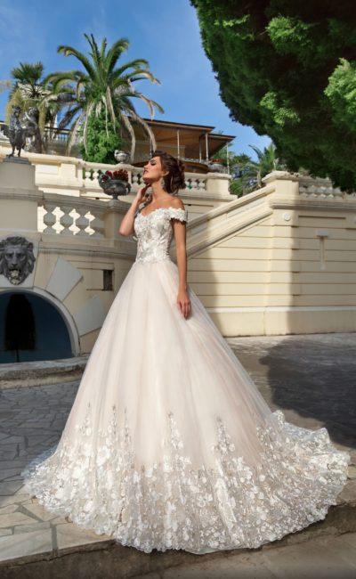 Пышное свадебное платье с открытым верхом и отделкой глянцевыми аппликациями.