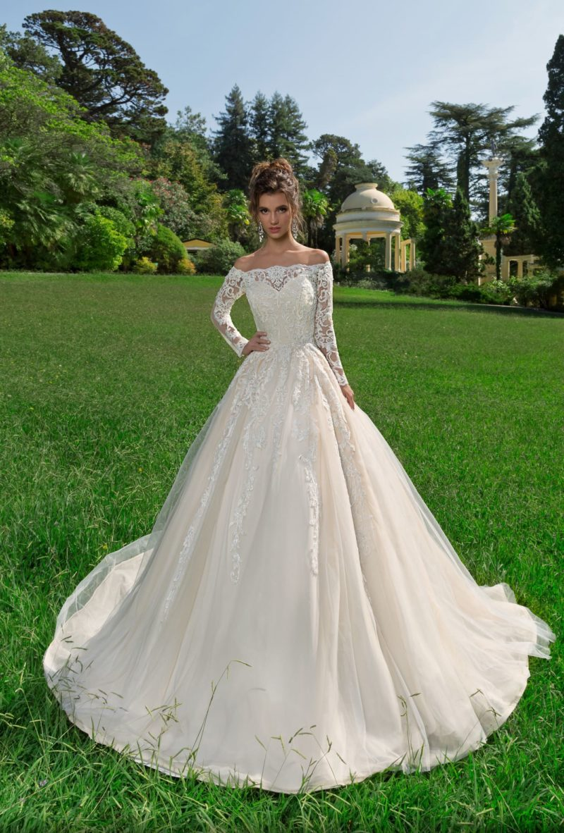 Пышное свадебное платье с длинным рукавом и стильным портретным декольте.