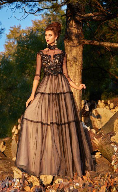Черно-бежевое вечернее платье длиной в пол с полупрозрачным рукавом.
