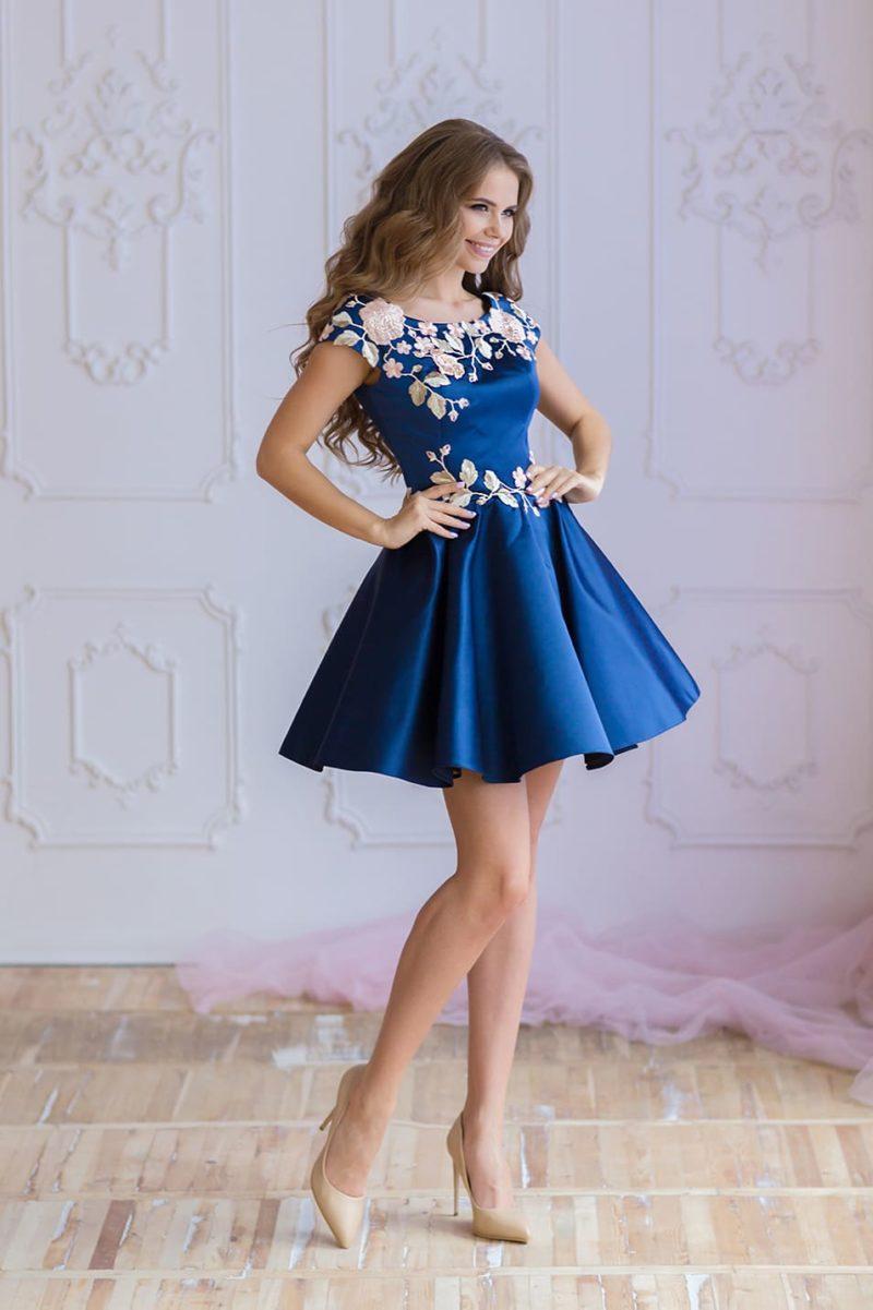 Синее вечернее платье с цветочной отделкой и короткой юбкой до середины бедра.