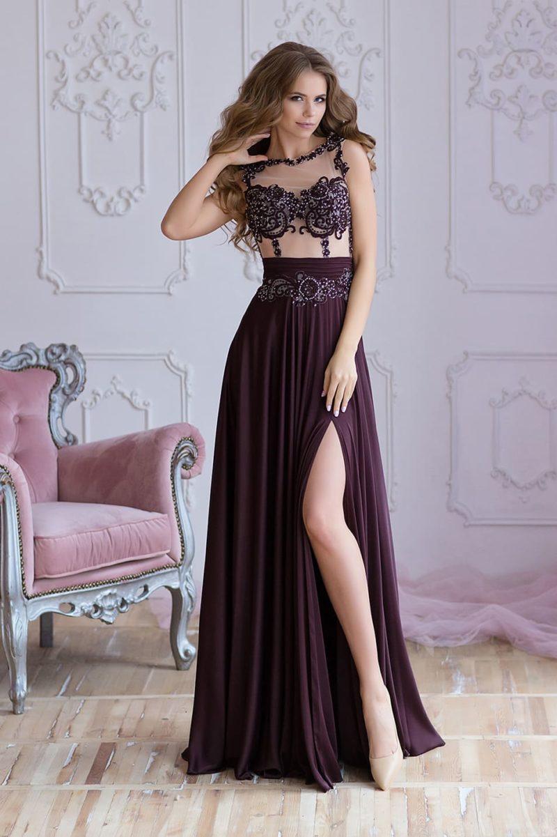 Изысканное вечернее платье с высоким разрезом на юбке и прозрачным верхом.