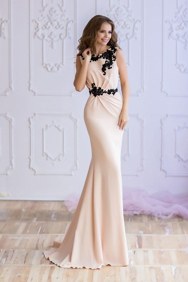 Бежевое вечернее платье «русалка» с закрытым лифом и черной отделкой.