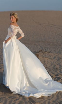 Пышное свадебное платье с портретным декольте и кружевным рукавом.