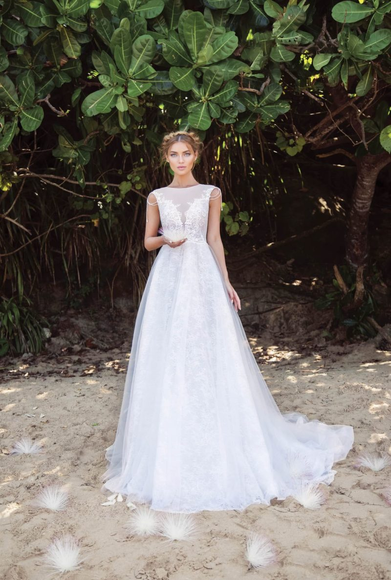 Свадебное платье с закрытым лифом без рукава и объемной юбкой со шлейфом.