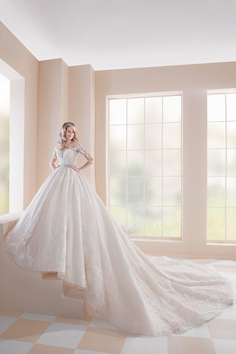 Свадебное платье цвета айвори с полупрозрачным рукавом и пышной юбкой.
