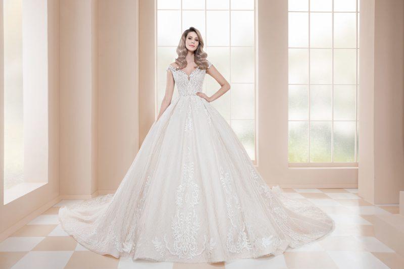 Свадебное платье пышного силуэта, декорированное кружевной тканью по всей длине.