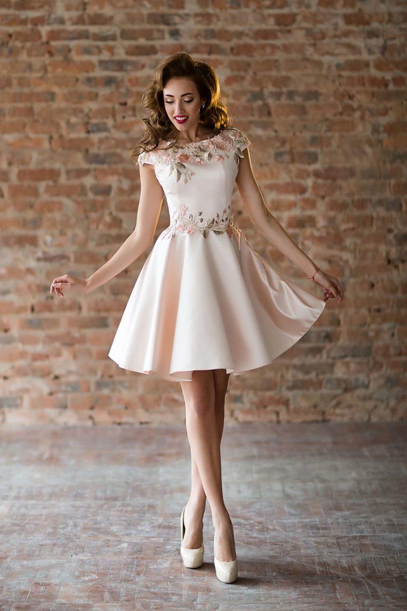 Розовое вечернее платье с кружевной отделкой и юбкой до середины бедра.
