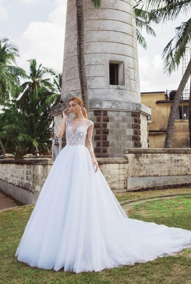 Пышное свадебное платье со шлейфом и длинным прозрачным рукавом.