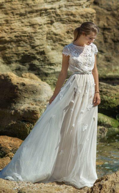 Закрытое свадебное платье с деликатным объемом юбки и коротким рукавом.