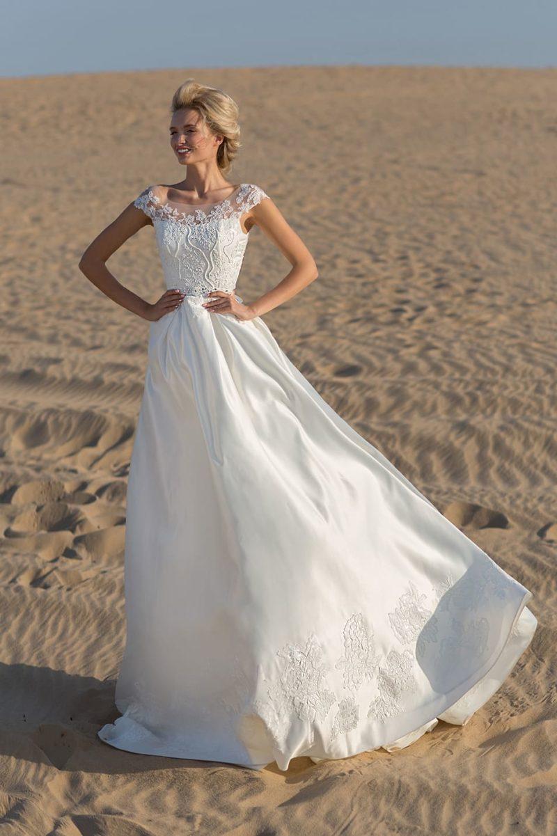 Роскошное свадебное платье с тонкой вставкой над лифом и бисерным поясом.