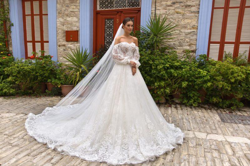 Свадебное платье с портретным декольте и длинным широким рукавом.