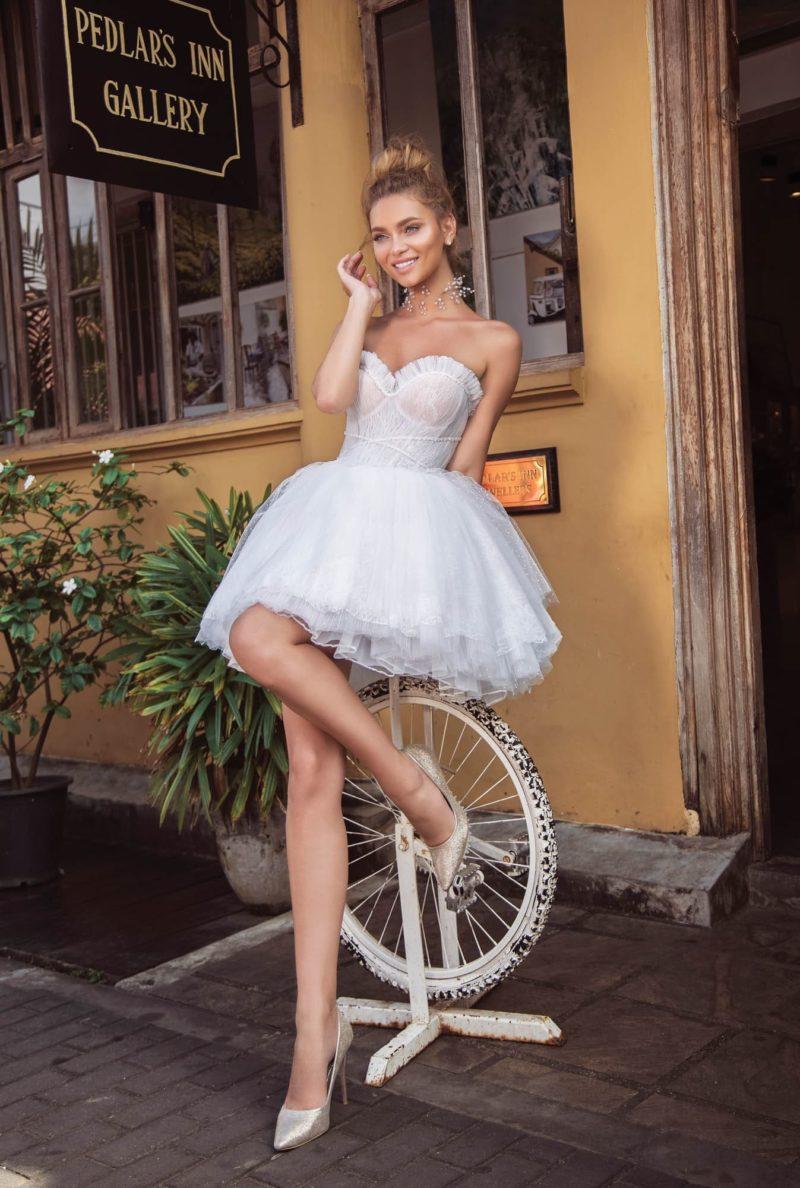 Короткое свадебное платье с открытым лифом и юбкой до середины бедра.