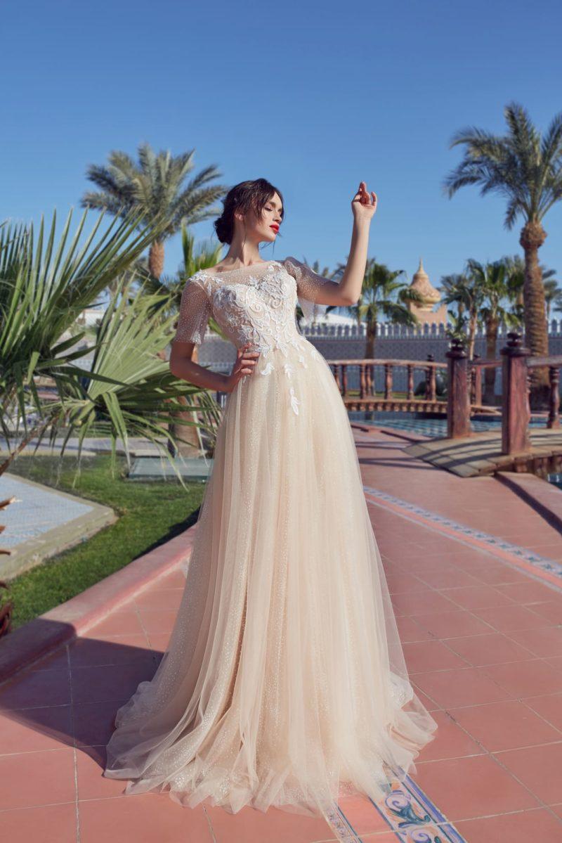 Свадебное платье с многослойным подолом и коротким полупрозрачным рукавом.
