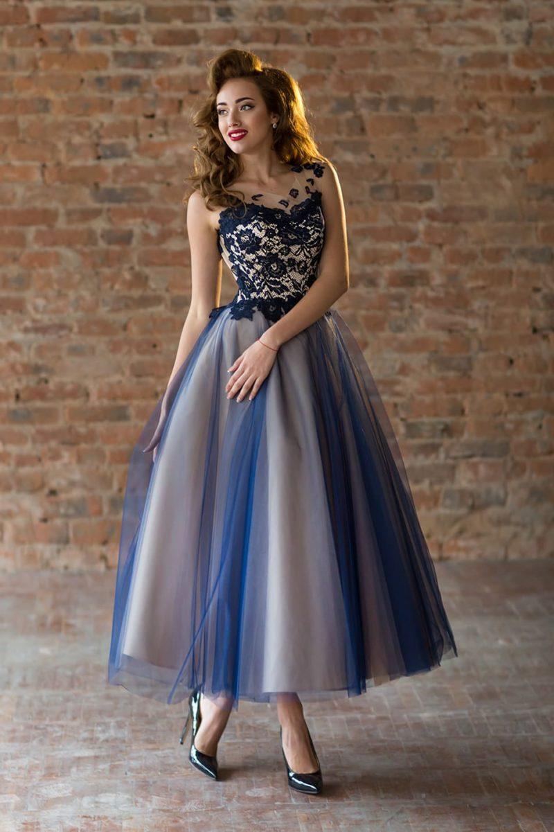 Вечернее платье с пышной юбкой до середины икры и кружевным декором верха.