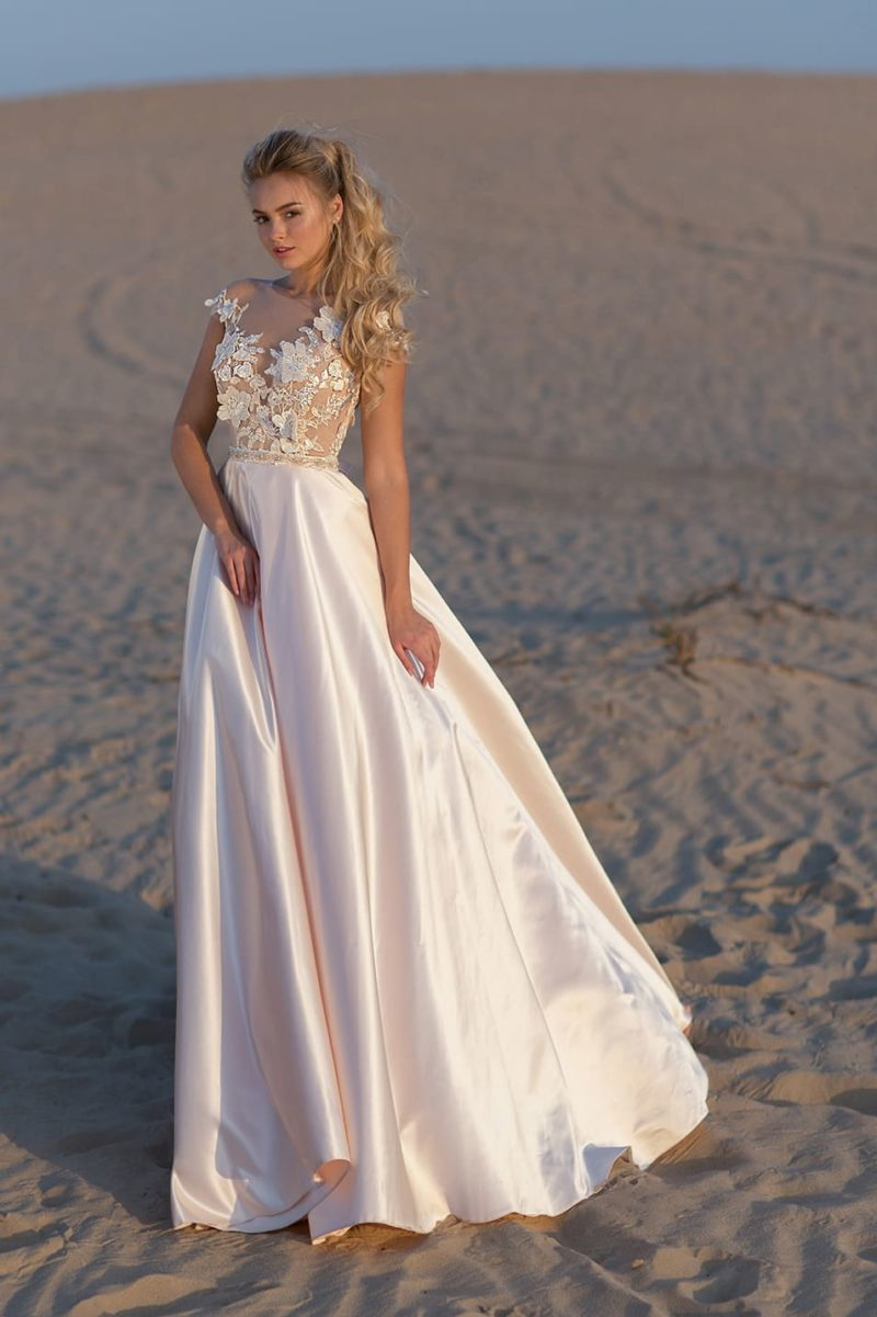 Кремовое свадебное платье с атласной юбкой и объемными бутонами на лифе.