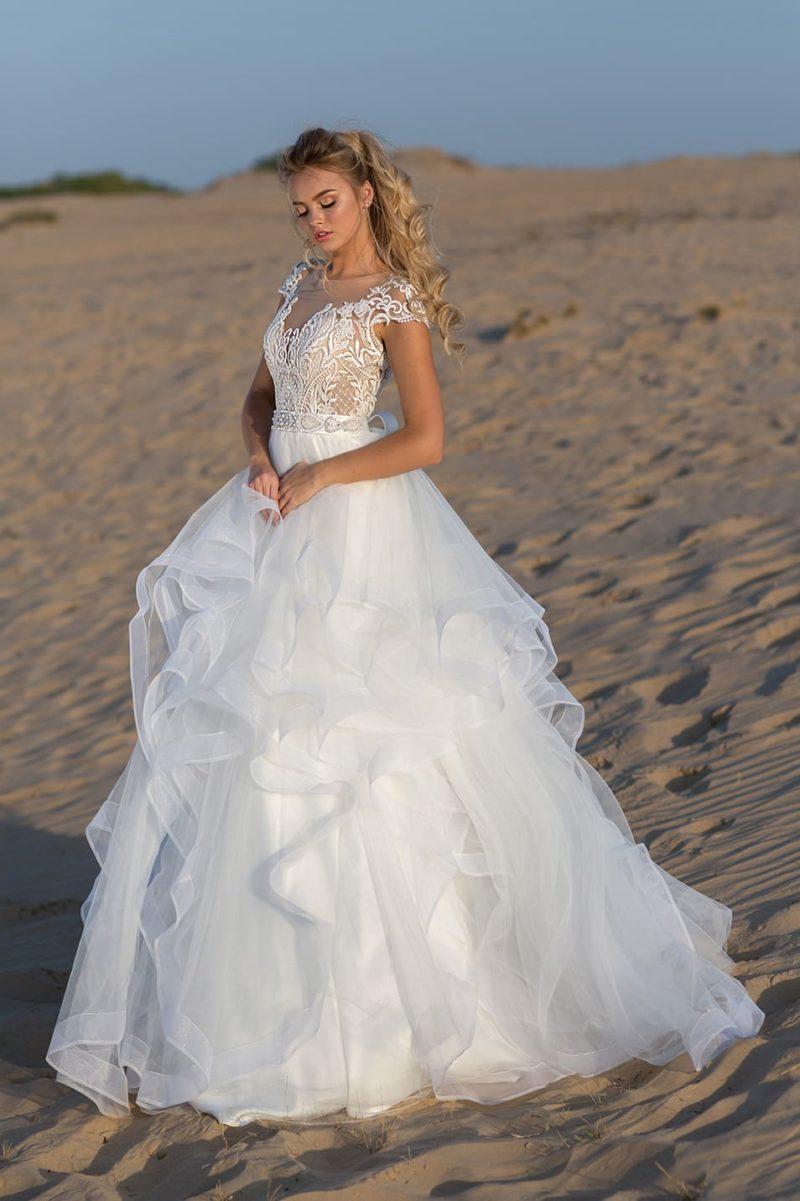 Кокетливое свадебное платье с кружевным декором и оборками по подолу.