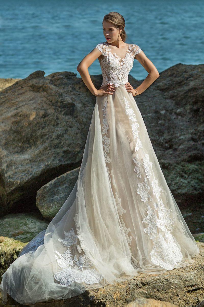 Бежевое свадебное платье с пышным низом и кружевом по всей длине.