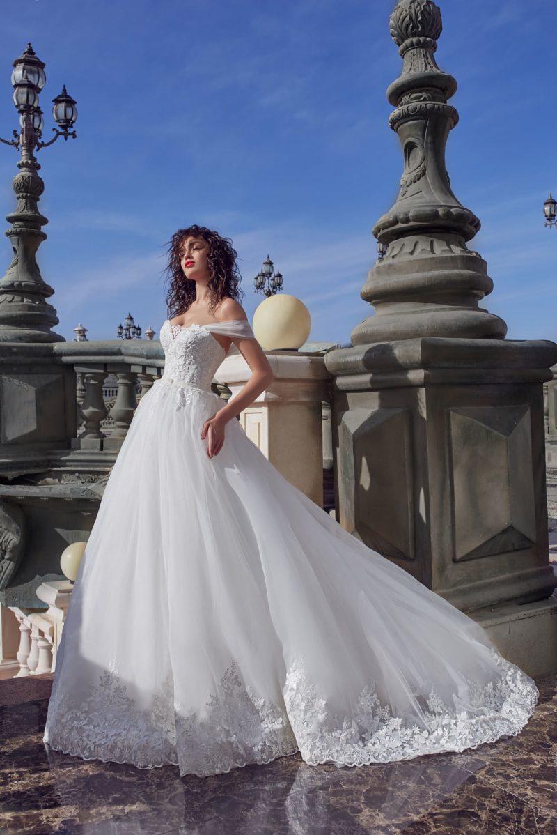 Пышное свадебное платье с фигурным низом подола и портретным лифом.
