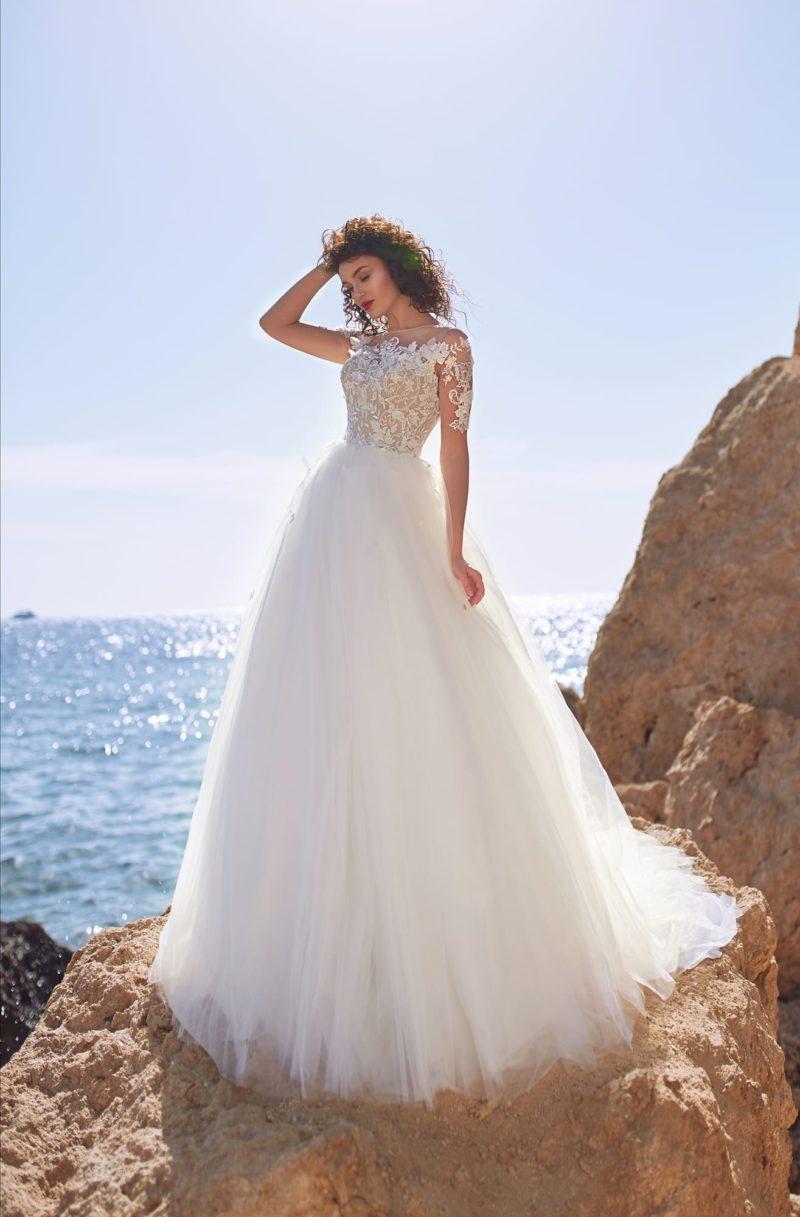 Свадебное платье с отделкой аппликациями и коротким рукавом.