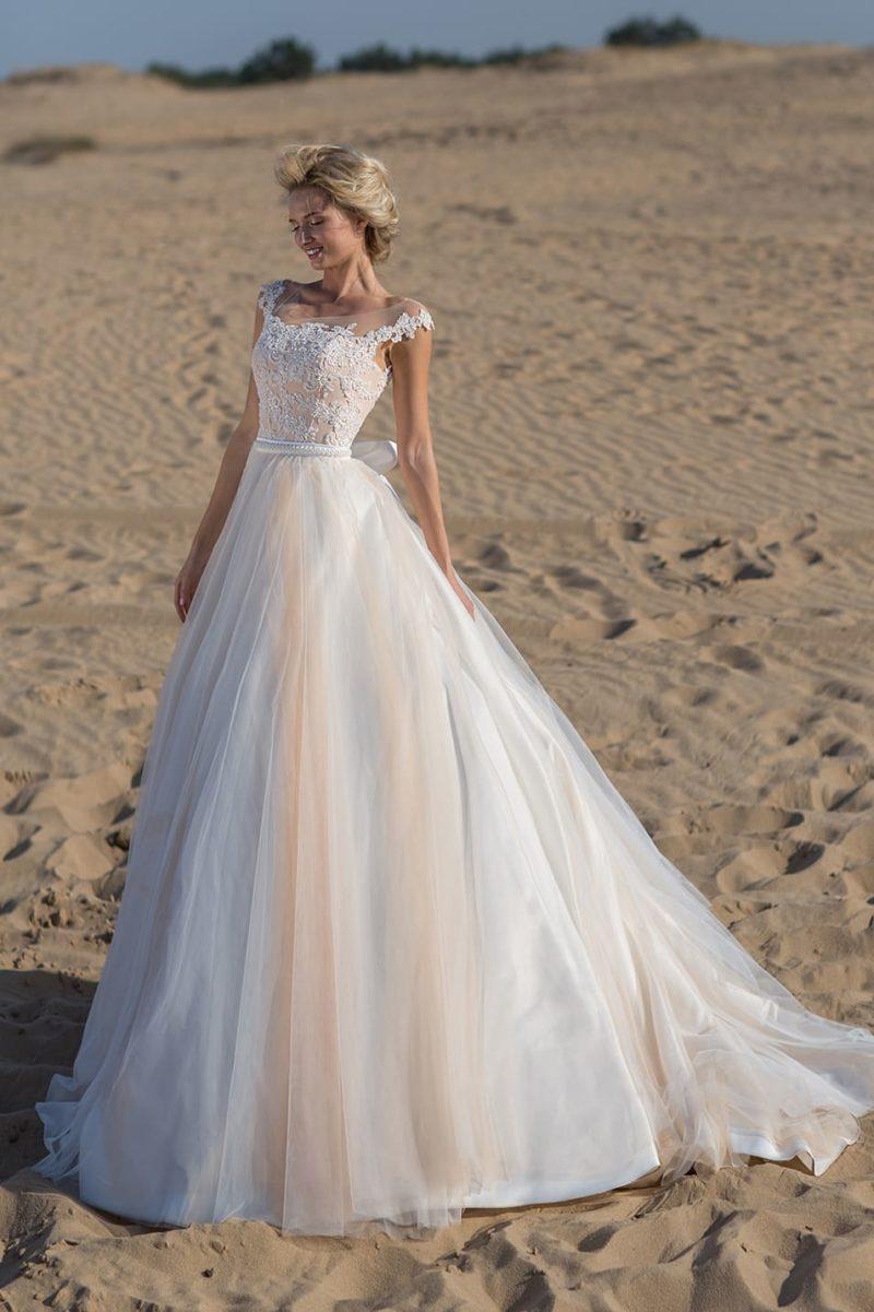 Пышное свадебное платье с кружевным верхом и персиковыми акцентами.
