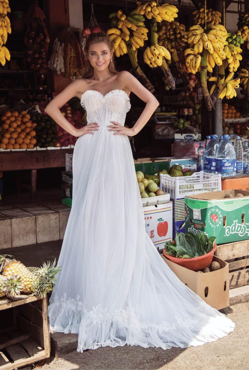Прямое свадебное платье с открытым лифом и отделкой оборками.