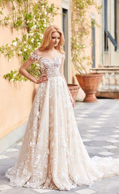 Свадебное платье цвета слоновой кости с портретным вырезом и пышной юбкой.