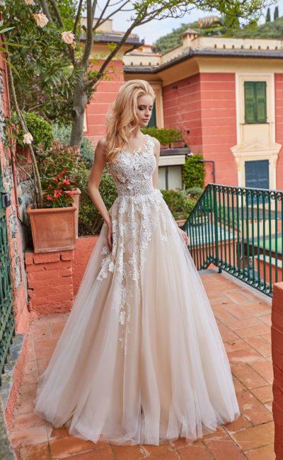 Пышное кремовое свадебное платье с открытым лифом и аппликациями.