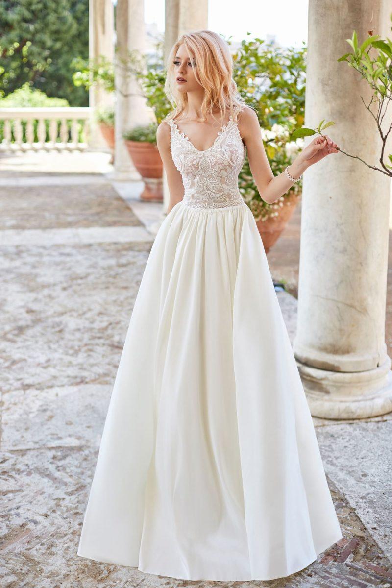 Свадебное платье с лаконичной юбкой и кружевным открытым верхом.