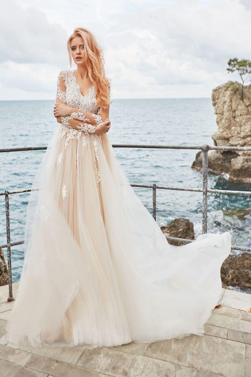 Воздушное свадебное платье бежевого оттенка с длинным полупрозрачным рукавом.