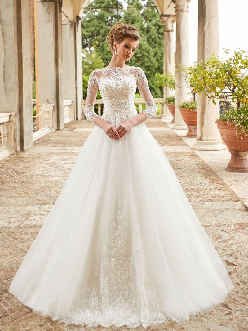 Пышное свадебное платье с плотным кружевным декором и рукавом.