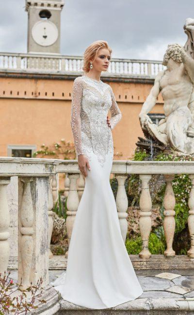 Облегающее свадебное платье с длинным рукавом и верхней юбкой.