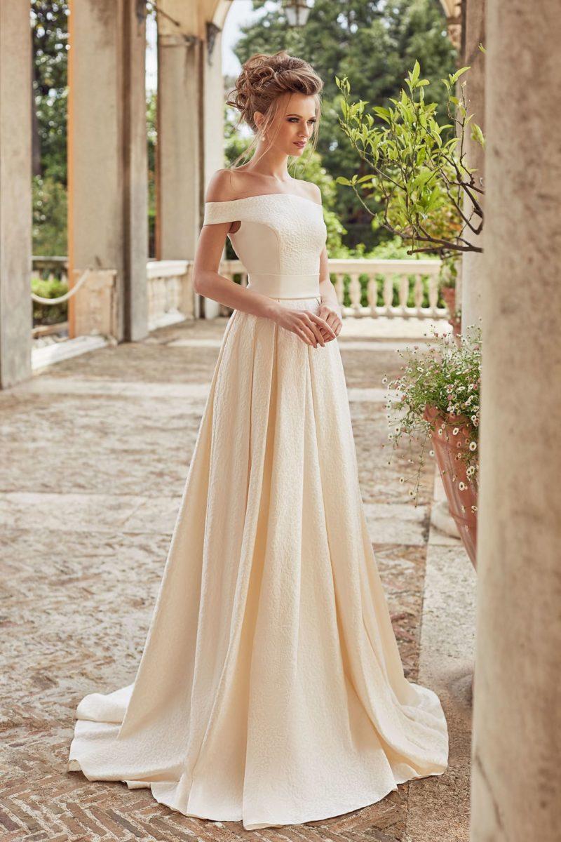 Кремовое свадебное платье с роскошной юбкой и портретным декольте.