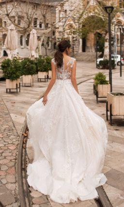 Свадебное платье с многослойной юбкой и кружевными аппликациями.