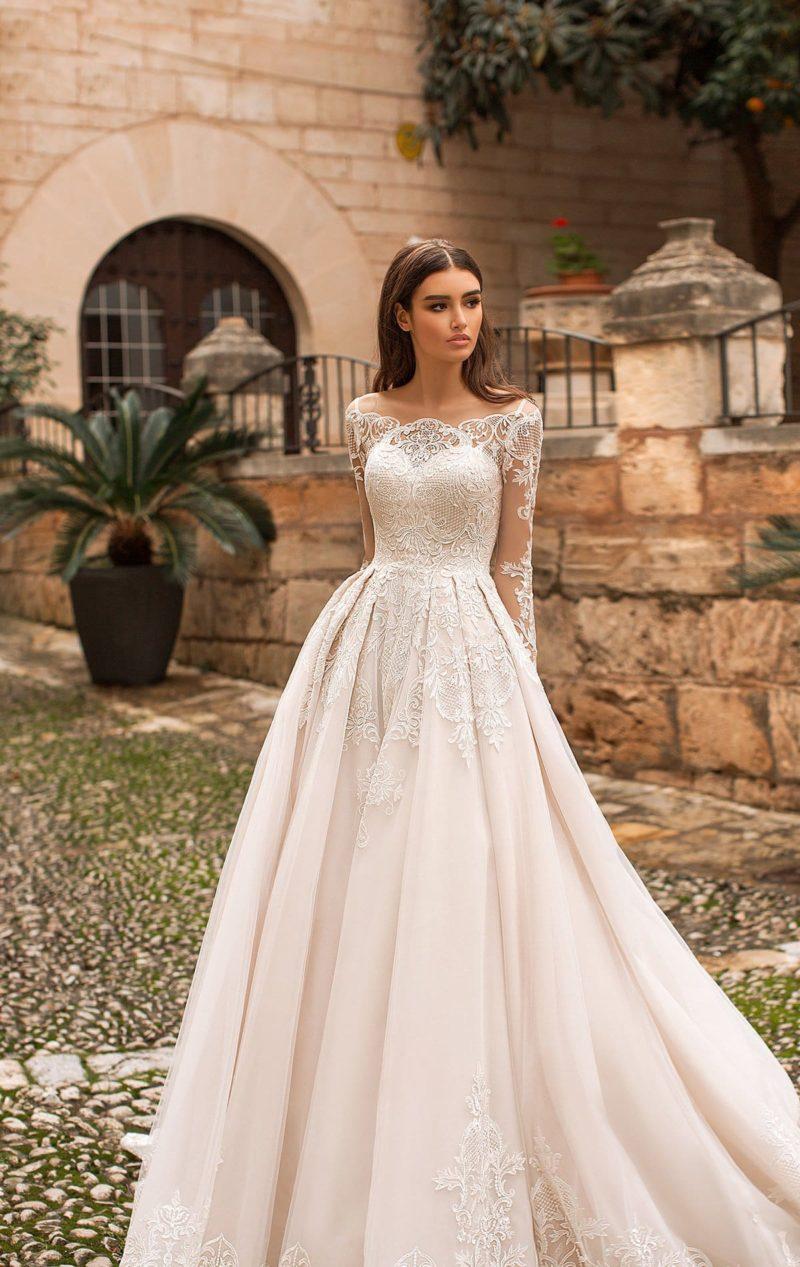 Свадебное платье пышного силуэта с длинными рукавами и складками на юбке.