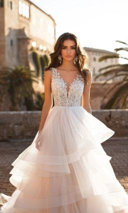 Воздушное свадебное платье с многоярусным подолом и кружевным верхом.